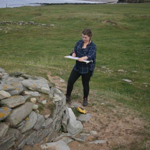 Archaeology student sketching at dig site